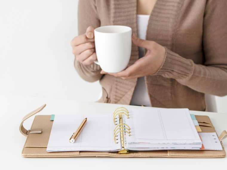 Woman holding coffee with planner