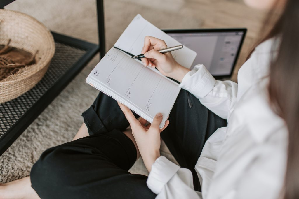 Image of woman writing in day planner